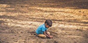 Kid playing on his own in sand